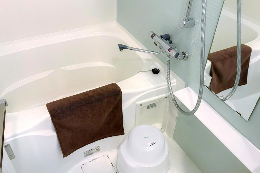 シンプルかつ整えられたバスルーム。アクアグリーンの壁面で爽やかさをプラス