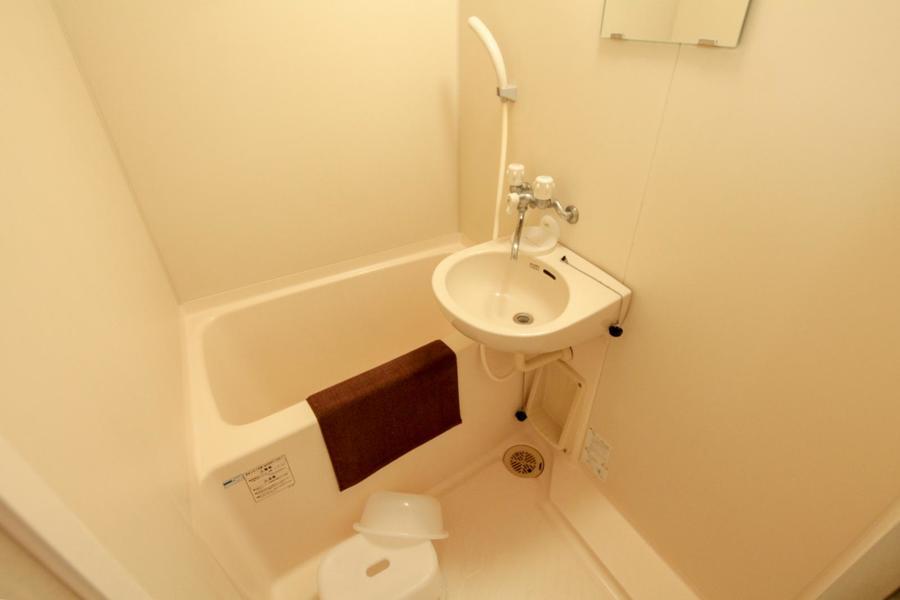 コンパクトながら清潔感あるバスルーム。洗面器などのお風呂用品もご用意しています