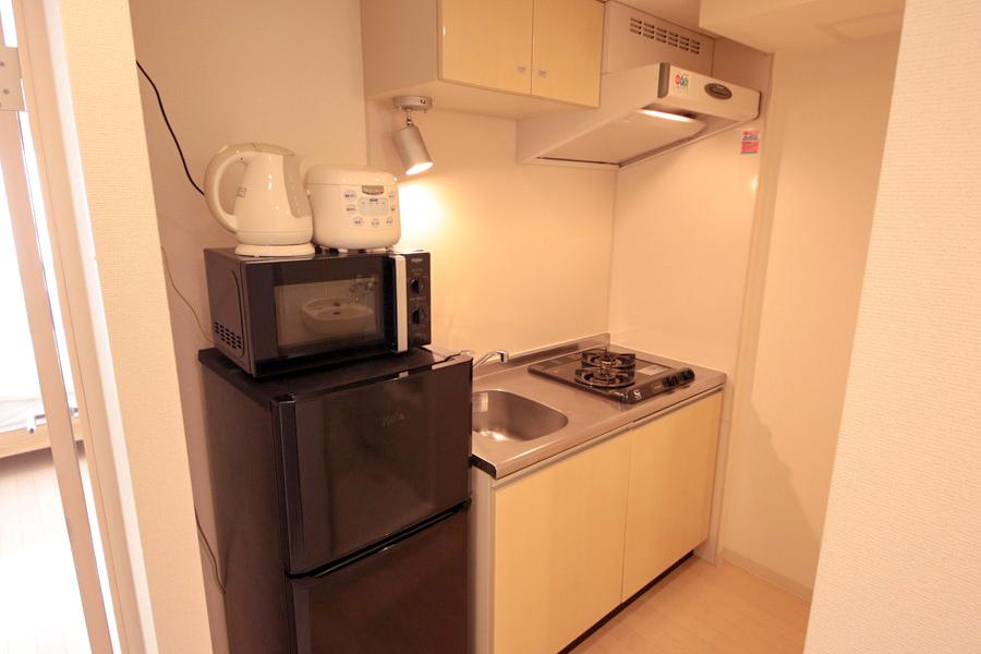 電子レンジや冷蔵庫などは使いやすく配置。スポットライトの照明もオシャレです