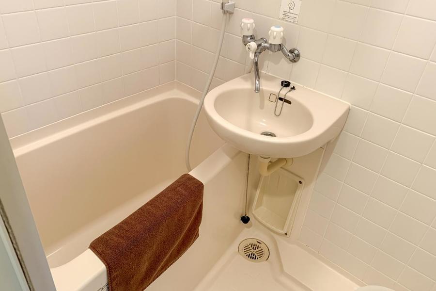 オフホワイトのタイルが清潔感あふれるバスルーム