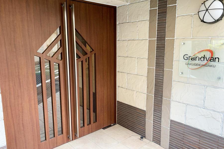 デザイン性に富んだエントランスドア。周辺はコンビニ、ファミレスが豊富に揃います