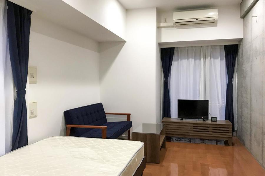 シンプルなお部屋の中、一面だけコンクリート打ちっぱなしの壁面がアクセントに