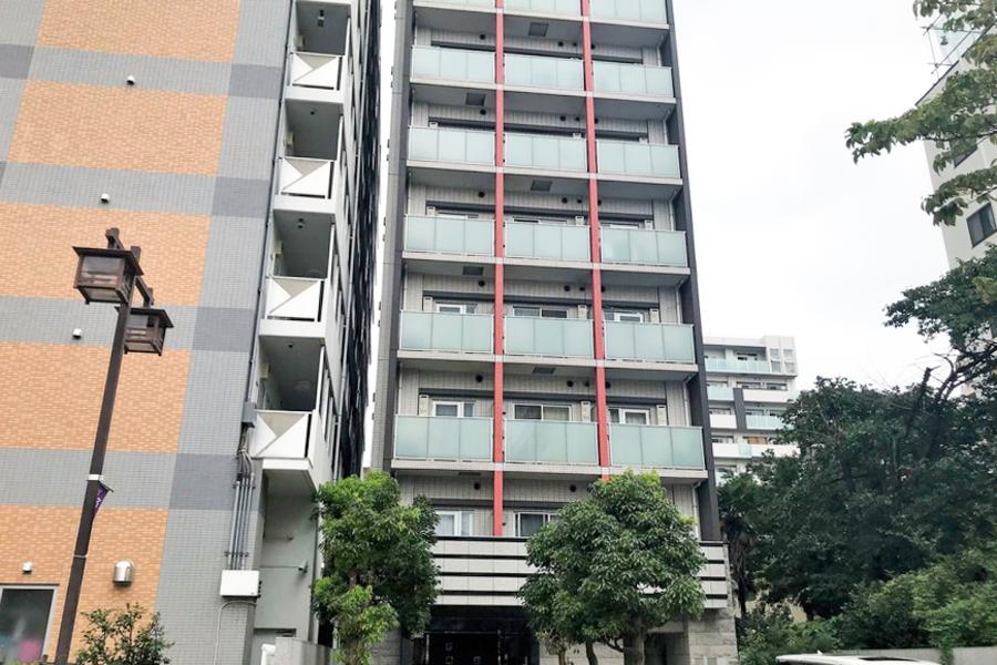 赤い2本のラインが特徴の外観。周囲はマンション、商業ビルが並ぶエリアです
