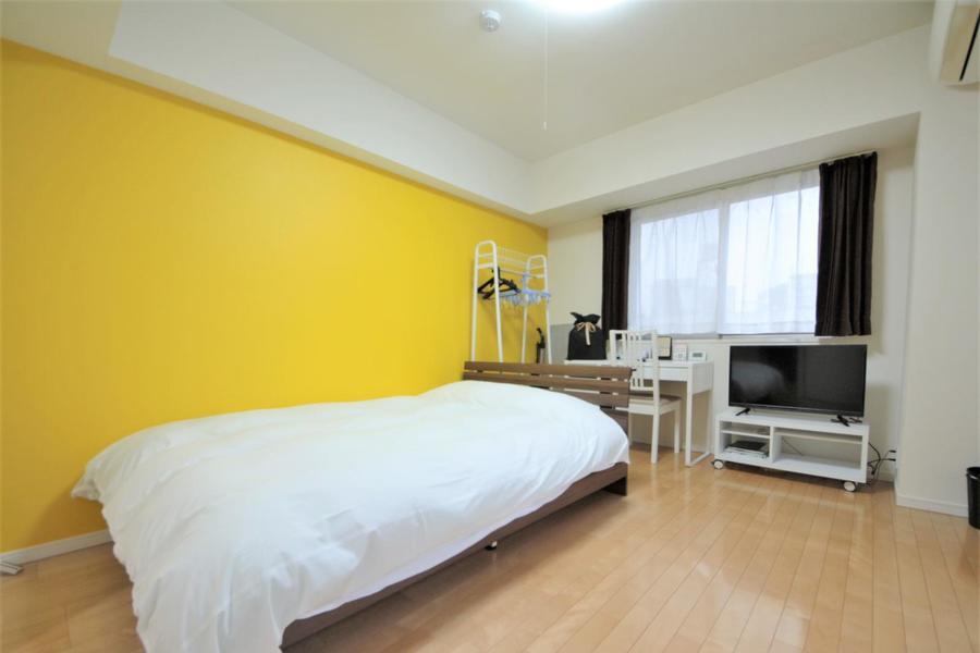 黄色い壁紙が目を引くゆったりとしたお部屋です