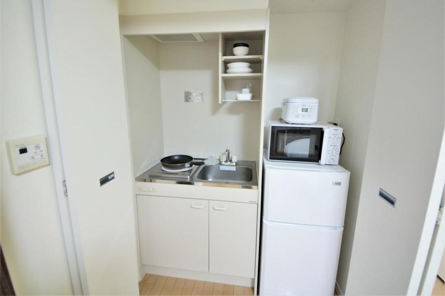 キッチンはコンパクトサイズ。食器などをおける吊り棚付