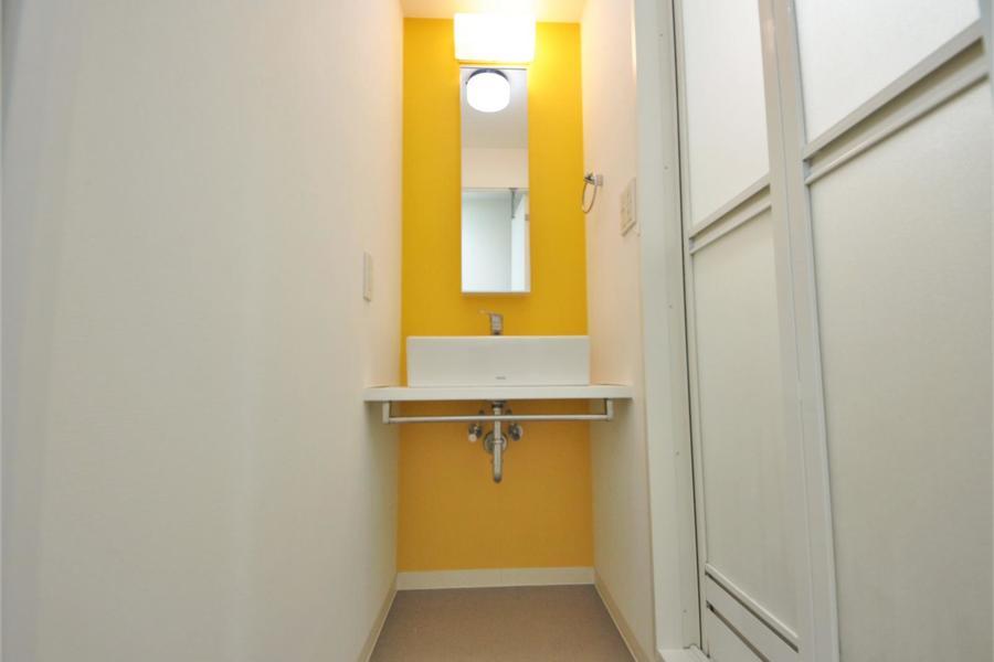 黄色い壁がおしゃれなすっきりとした洗面台