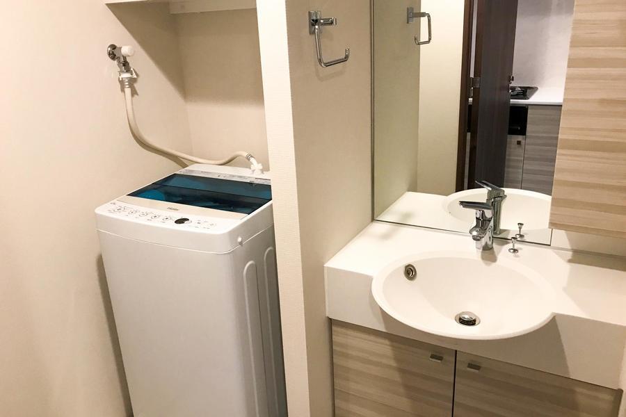 木目の扉が特徴の洗面台。鏡は大きく上半身をしっかり写せます