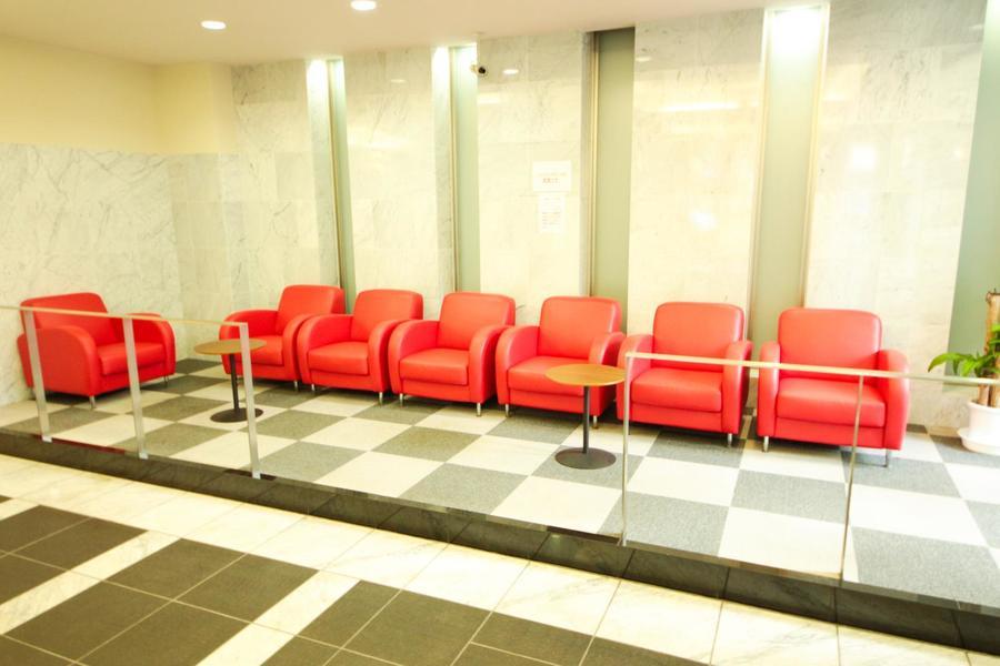 エントランスホールは落ち着いた色合い。そんな中に真っ赤なソファが彩りをプラス