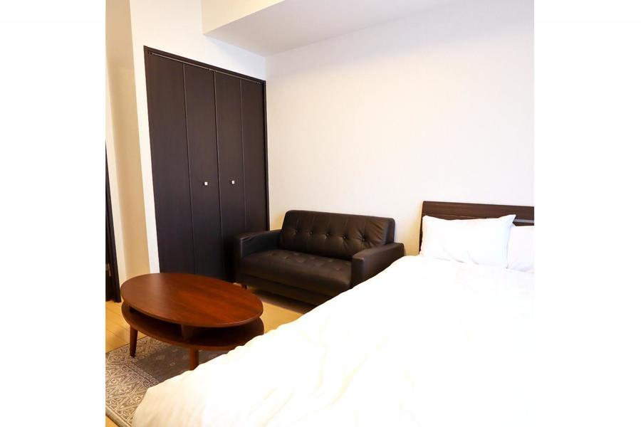 セミダブルサイズのベッドと大きめのソファを備えた1Kルーム