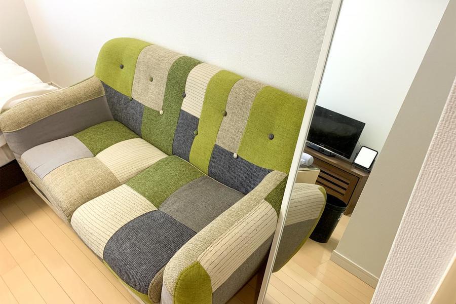 パッチワーク模様がポイントのソファ。身だしなみチェックに便利な姿見もセッティング済