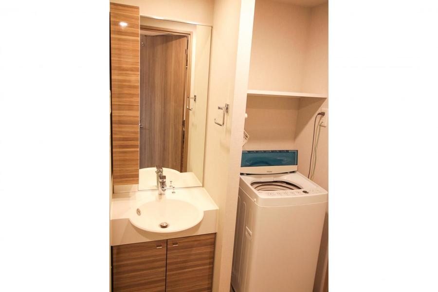 大きな鏡が特徴の洗面台。木目扉の収納もポイントです