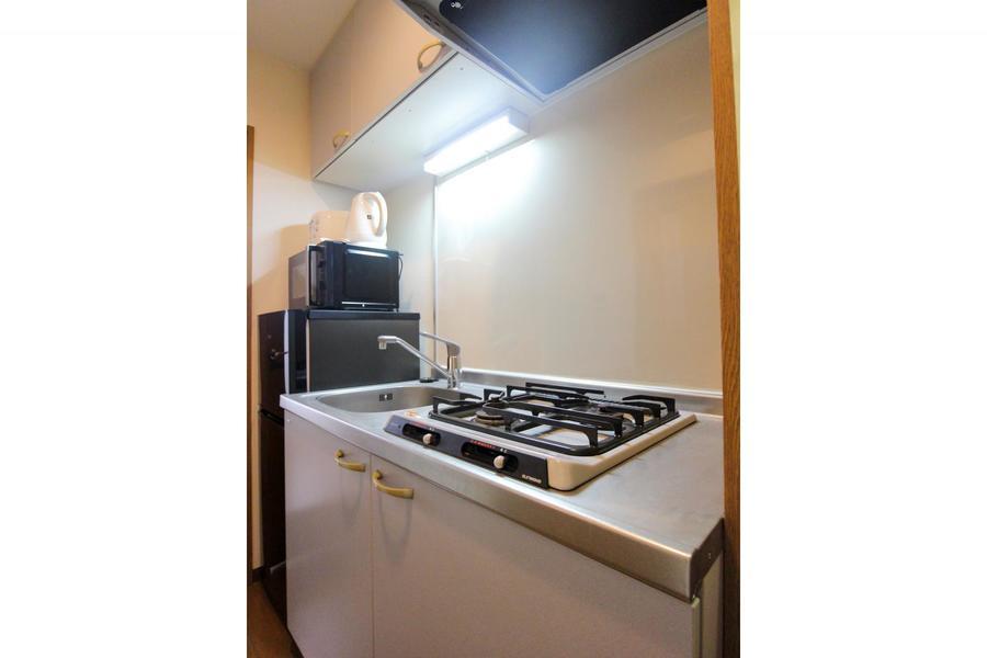 コンロは二口のガスタイプ。冷蔵庫や電子レンジなども手の届く範囲に設置しています