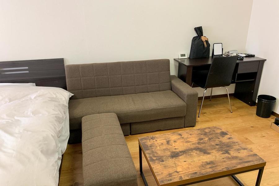 ベッド横にはソファを設置。オットマンつきで足を伸ばしてゆったりと