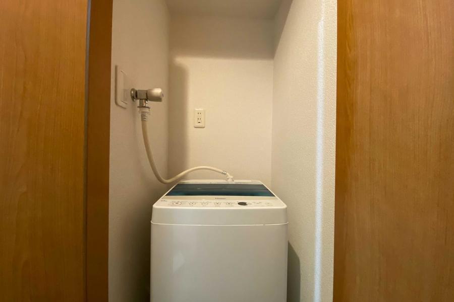 洗濯機は収納の中にございます。