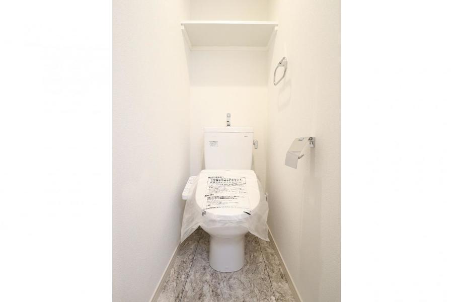 白基調のクロスにフローリングが目を引くトイレ