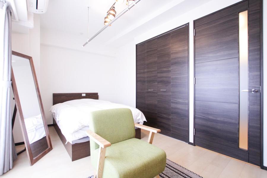 ベッドフレームや姿見の色合いも内装と合わせ、統一感のある空間に