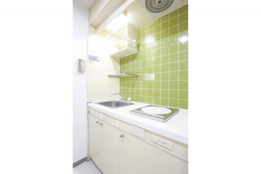 イエローグリーンのタイルがアクセントのコンパクトなキッチン
