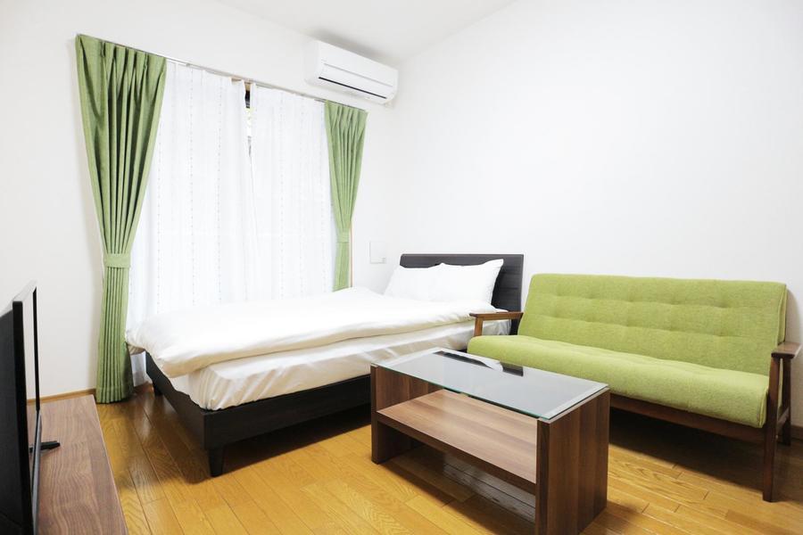 ダークブラウンの家具に緑のカーテン・ソファが映えます