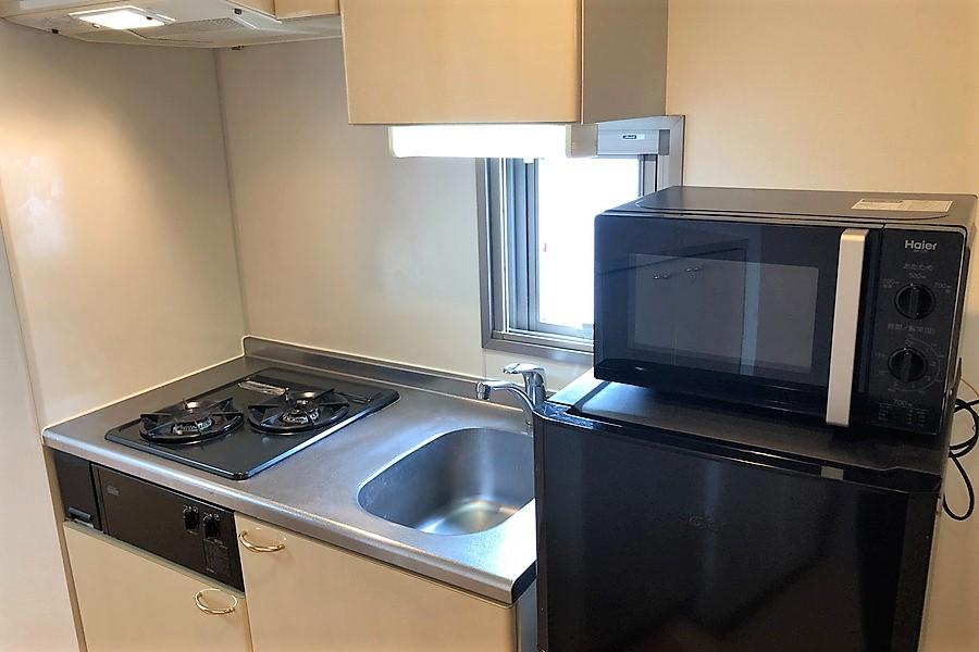 キッチンは上下段に収納棚を完備。さらに火力が安定するガスコンロを搭載しています