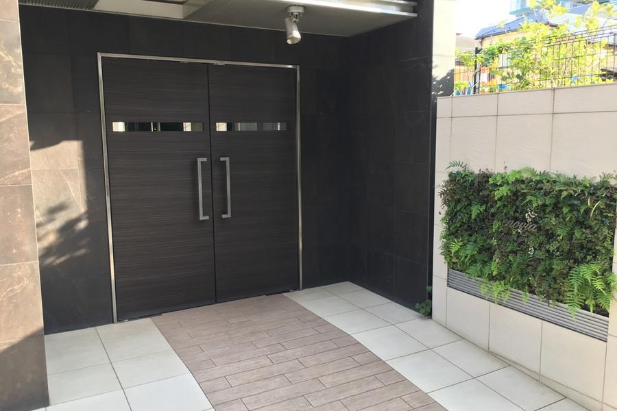 エントランスドアは重厚さ漂うブラック。うっすらと浮かぶ木目がシック
